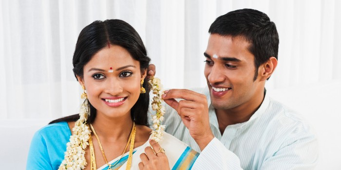 South Indian man putting gajra in his wifes hair