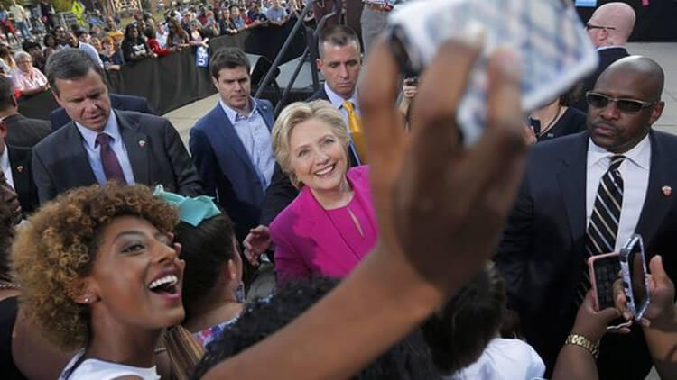 Democratic U.S. presidential nominee Hillary Clinton (C) poses for a selfie with an audience member at a campaign rally at Pitt Community College in Winterville, North Carolina, U.S., November 3, 2016.  REUTERS/Brian Snyder