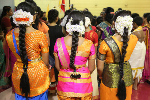Tamil Hindu children listen to prayers after performing a Bharatnatyam dance during the Nambiyaandaar Nambi Ustavam Thiruvizha pooja at a Hindu Temple in Ontario, Canada, on 19 July 2017. This pooja is part of the 15 day long festival that honours Lord Ganesh which culminates with the extravagant chariot procession. During this Puja an idol of Lord Ganesh is paraded around the temple as prayers are performed. (Photo by Creative Touch Imaging Ltd./NurPhoto via Getty Images)