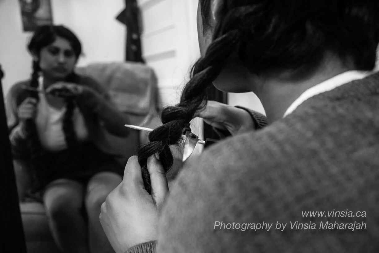Image of a South Asian woman cutting her braided hair with a pair of scissors.