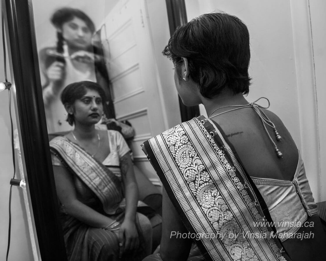 A South Asian woman in a saree and short cropped hair, is staring at her reflection in the mirror. In the background there is a ghost of herself in the past when she cut her braid off.